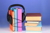 Auriculares en libros sobre fondo azul — Foto de Stock