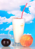 Delicious milk shakes with fruit on table on sky background — Stock Photo