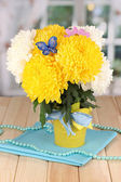 Beautiful chrysanthemum in pail on wooden table on window background — Stock Photo