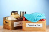 Donation boxes with clothing and food on blue background close-up — Stock Photo