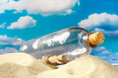 Glass bottle with note inside on sand, on blue sky background — Stock Photo