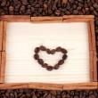 Frame of coffee beans with heart on wooden background — Stock Photo