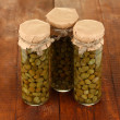 Glass jars with tinned capers on wooden background close-up — Stock Photo