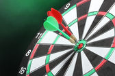 Dart board with darts on green background — Stock Photo