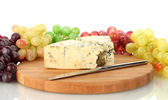 Cheese with mold on the cutting board with grapes on white background close — Stock Photo