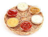 Various sauces on wicker mat isolated on white — Stock Photo
