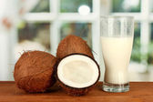 Glass of coconut milk and coconuts on wooden table close-up — Stock Photo