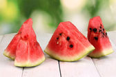 Sweet watermelon slices on wooden table on natural background — Stock Photo