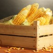 Fresh corn in box, on wooden table, on grey background — Stock Photo
