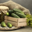 Fresh cucumbers in wooden box, pickles and dill, on grey background — Stock Photo