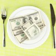 Banknotes on plate on green tablecloth close-up — Stock Photo #12797468