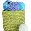 Colorful yarn for knitting in green basket isolated on white - Stock Photo