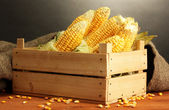 Fresh corn in box, on wooden table, on grey background — Foto de Stock