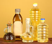 Olive and sunflower oil in the bottles and small decanters on yellow backgr — Stock Photo