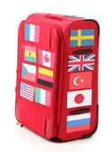 Red suitcase with many stickers with flags of different countries isolated — Stock Photo