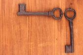 Zwei antike schlüssel auf hölzernen hintergrund — Stockfoto