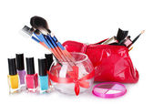 Make-up brushes in glass vase and cosmetics isolated on white — Stock Photo