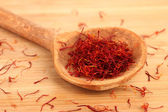 Stigmas of saffron in wooden spoon on wooden background close-up — Stock Photo