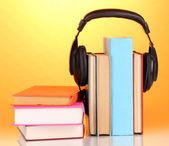 Kopfhörer auf bücher über orangefarbenen hintergrund — Stockfoto