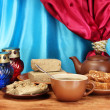 Teapot with cup and saucers with oriental sweets - sherbet and halva on woo - Stockfoto
