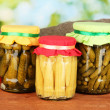 Jars with canned vegetables on green background close-up - Foto Stock