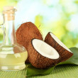 Decanter with coconut oil and coconuts on green background - Stockfoto