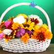 Royalty-Free Stock Photo: Beautiful bouquet of bright flowers in white basket on wooden table on gree
