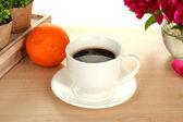 šálek kávy, oranžové a květiny na stole v kavárně — Stock fotografie