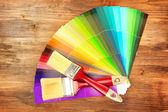 Pinceles y brillante paleta de colores sobre fondo de madera — Foto de Stock