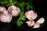 Young garlic peeled and onion with greenery on black background close-up — Stock Photo