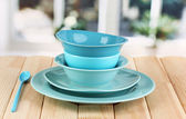 Blue tableware on wooden table on window background — Stock Photo