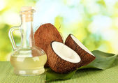Decanter with coconut oil and coconuts on green background — Fotografia Stock