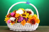 Beautiful bouquet of bright flowers in white basket on wooden table on gree — Stock Photo
