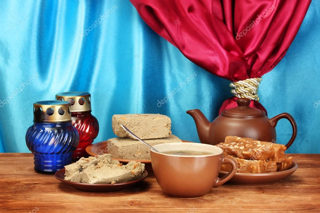 Teapot with cup and saucers with oriental sweets - sherbet and halva on wooden table on a background of curtain close-up — Stock Photo #12844078
