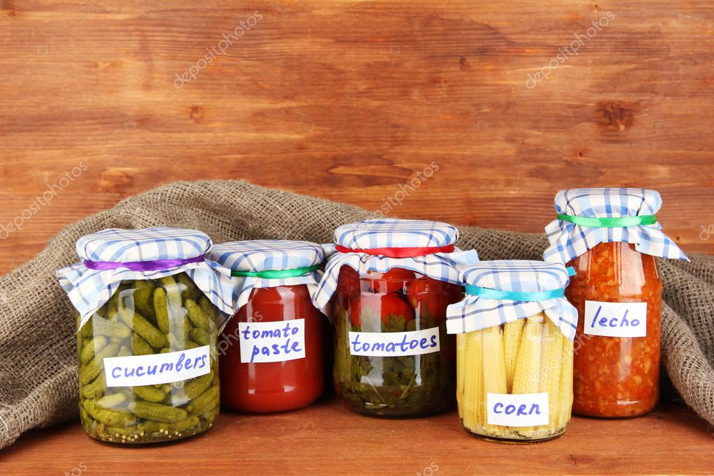 Jars with canned vegetables on green background close-up — Stock Photo #12844134