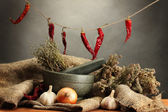 Dried herbs in mortar and vegetables, on wooden table on grey background — Stock Photo