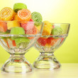 Colorful jelly candies in in glass bowls on green background — Stock Photo