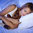 Young beautiful woman with toy bear sleeping on bed in bedroom — Stock Photo #12866186