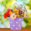 Purple bucket with white polka-dot with flowers on green background — Stock Photo #12867013