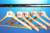 Wooden clothes hangers as sale symbol on blue background — Stock Photo