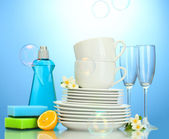 Empty clean plates, glasses and cups with dishwashing liquid, sponges and l — Stock Photo