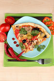 Delicious slice of pizza on color plate with ingredients around close-up on — Stock Photo