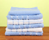 Kitchen towels on wooden table on green background close-up — Stock Photo