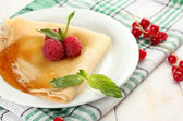 Delicious pancake with berries and honey on plate on wooden table — Stock Photo