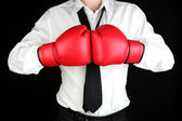 Businessman in boxing gloves isolated on black — Stock Photo