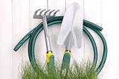 зеленая трава и садовый инвентарь на деревянных фоне — Стоковое фото