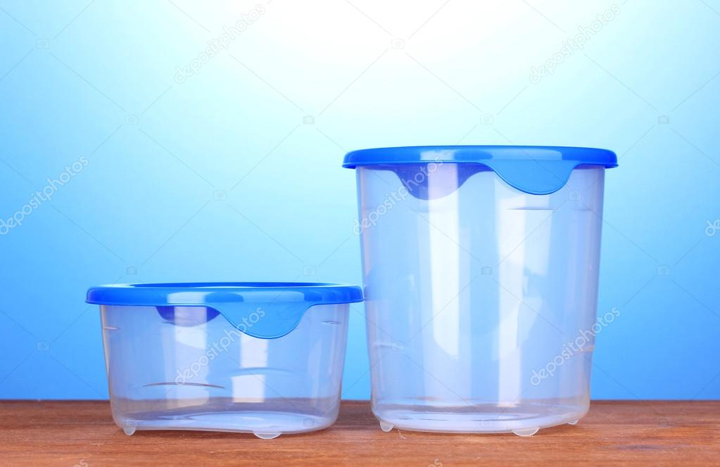 Plastic containers for food on wooden table on blue background — Stock Photo #12860491