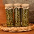 Stock Photo: Glass jar with tinned capers on wooden background close-up