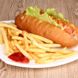 Appetizing hot dog with fried potatoes on plate on wooden table - Stock Photo