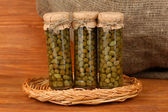 Glass jar with tinned capers on wooden background close-up — Stock Photo